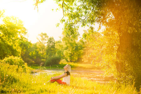 Photo for beautiful woman having rest under huge tree in sunset time outside. Sunset people. Lonely woman enjoying nature landscape in evening. Summer or spring day. Girl sitting on grass Color horizontal image - Royalty Free Image