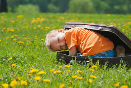Photo for Cute little funny child trying to hide inside of vintage brown suitcase. Boy laughs and smiles happily while playing outdoors on green grass lawn full of yellow dandelion flowers on sunny spring day. - Royalty Free Image