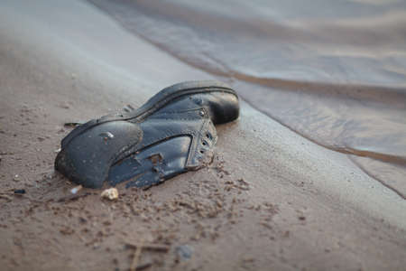 Photo pour Dusty old shoe abandoned on river coat - image libre de droit