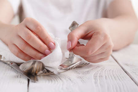 Photo for Woman is cleaning and drying spoons for catering. - Royalty Free Image