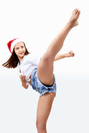 Photo for Beautiful girl in a Santa Claus hat is beating kick - Royalty Free Image