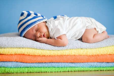 Photo pour Sleeping newborn baby on colorful towels stack - image libre de droit