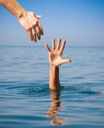 Foto de helping hand giving to drowning man in sea - Imagen libre de derechos