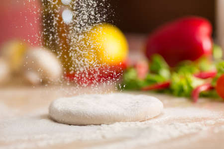 Photo pour Dough for Italian pizza preparation. Falling flour. - image libre de droit