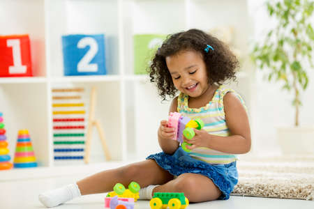 Photo pour Kid girl playing toys at home or kindergarten - image libre de droit