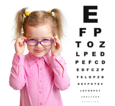 Foto de Smiling girl putting on glasses with blurry eye chart behind her - Imagen libre de derechos