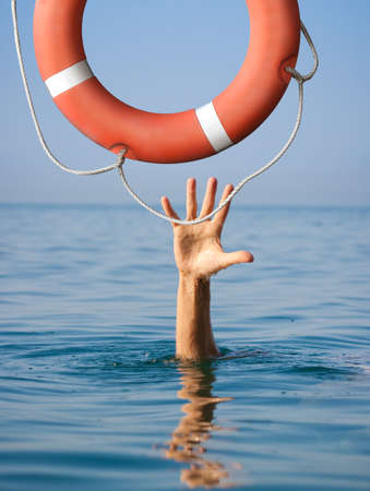 Foto de Lifebuoy for drowning man in sea or ocean water. Insurance concept. - Imagen libre de derechos