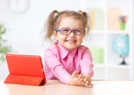 Photo pour Happy kid with tablet PC in glasses as early education concept - image libre de droit