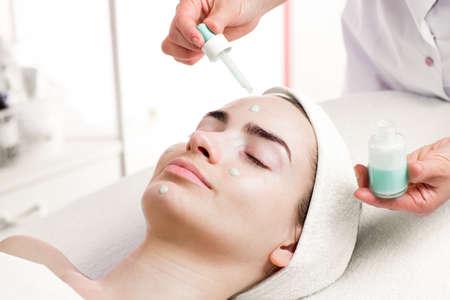 Photo pour Serum facial treatment of young woman in spa salon - image libre de droit