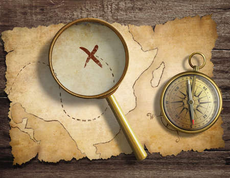 Photo pour aged antique nautical compass and magnifying glass on table with treasure map - image libre de droit