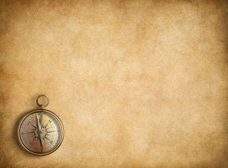 Foto de Brass compass on blank vintage paper background - Imagen libre de derechos