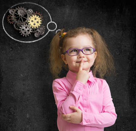 Foto de kid in glasses with bright idea standing near school blackboard in classroom - Imagen libre de derechos