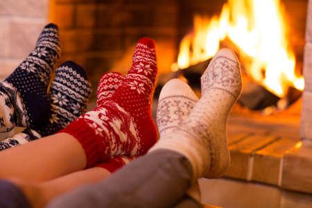 Photo pour Feet in wool socks near fireplace in winter time - image libre de droit
