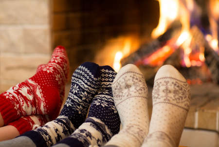 Photo pour Feet in wool socks near fireplace in winter time - image libre de droit