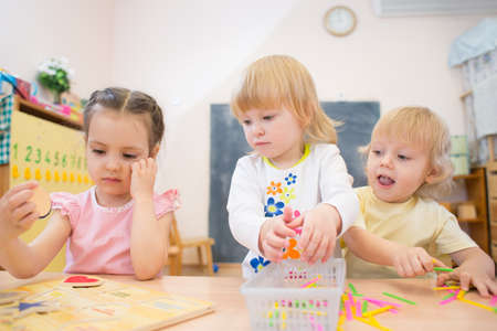Photo for kids group playing puzzle and other board games in day care centre - Royalty Free Image