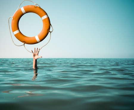 Foto de Drown man with rised hand getting lifebuoy help in sea or ocean - Imagen libre de derechos