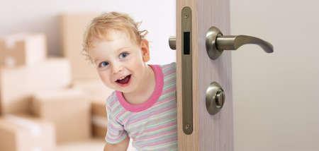 Foto de happy kid behind door in new room - Imagen libre de derechos