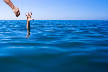 Foto de Help hand for drowning man life saving in sea water - Imagen libre de derechos