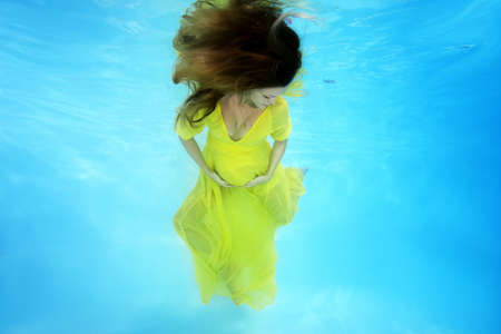 Photo for Young pregnant woman in a bright yellow dress posing underwater - Royalty Free Image