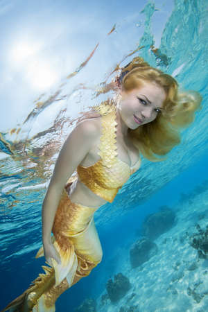 Foto de Golden-haired mermaid swims underwater surface in blue water, Indian Ocean, Maldives - Imagen libre de derechos
