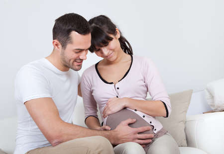 Portrait of happy pregnant woman and her husband on sofa at home