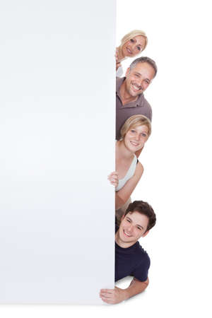 Happy family with two teenage children holding up a blank placard or sign with copyspace for your advertising of announcement