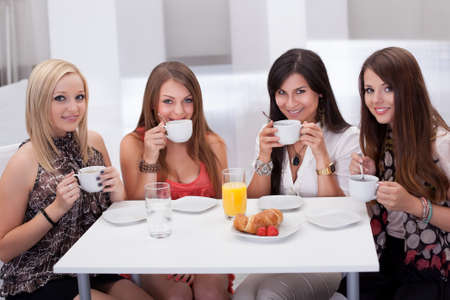 Four stylish attractive young female friends seated at a table chatting over coffee