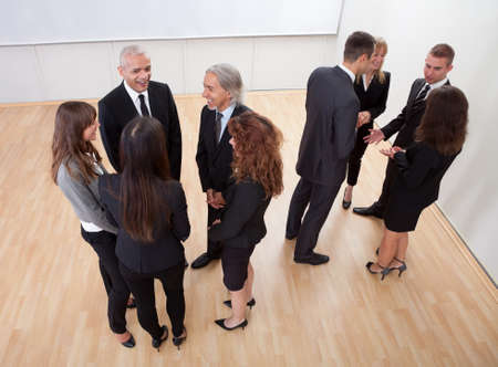 High angle view of professional business people standing around in informal groups chatting as they wait for a meeting