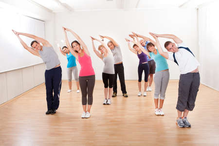 Large group of diverse people in a pilates class exercising in a gym doing core stretching