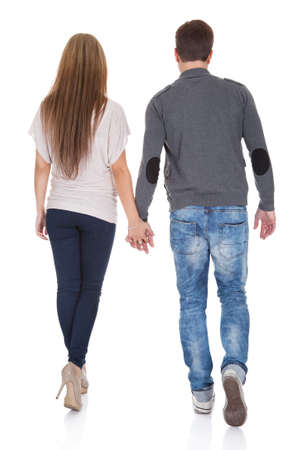 Sweet partners hold each others' hands while walking.