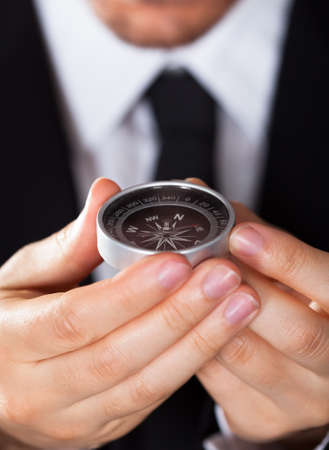 Businessman looking at a compass which he is holding in his hand with focus to the compass