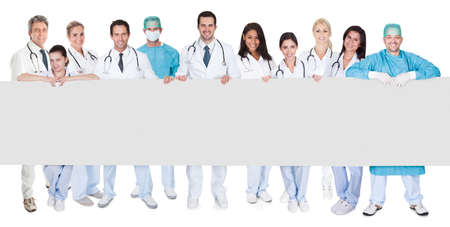 Photo for Group of doctors presenting empty banner. Isolated on white - Royalty Free Image