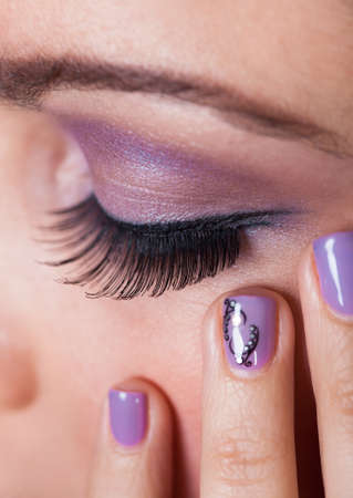 Close-up Of Woman\'s Eye With Purple Eyeshadow And Finger Nail Varnish