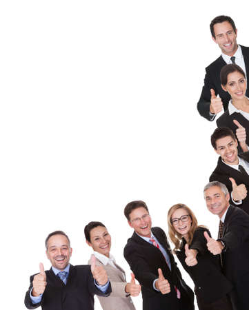 Laughing group of business executives giving a thumbs up of approval and victory as they celebrate a successful outcome isolated on white