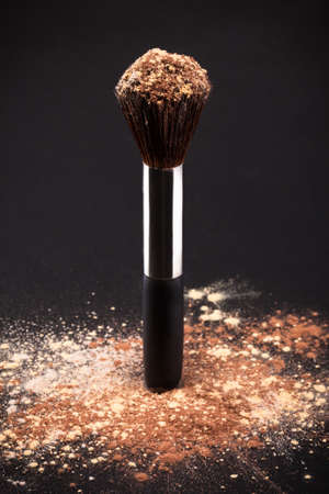 Makeup Brush And Cosmetic Powder Isolated On Black Background