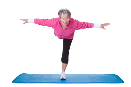 Photo pour Senior Woman Standing On One Leg And Exercising Over White Background - image libre de droit