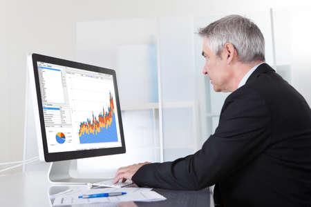 Foto de Mature Businessman Looking At Computer Showing Diagram - Imagen libre de derechos