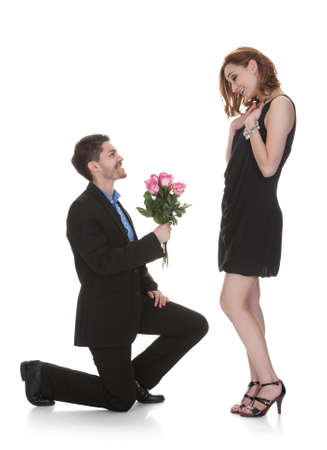Photo pour Young Man Offer Flower To Beautiful Woman Over White Background - image libre de droit