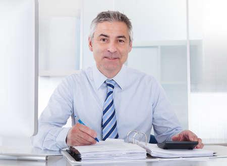 Photo pour Portrait Of Mature Businessman Calculating Finance At Office - image libre de droit