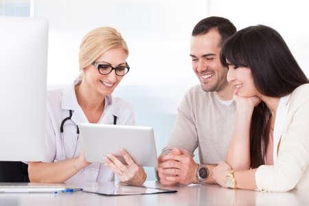 Foto de Happy Doctor Discussing With Couple In Clinic - Imagen libre de derechos