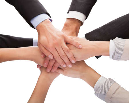 Photo for Close-up Of Businesspeople Hands Stacking Together Over White Background - Royalty Free Image