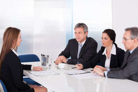 Photo for Group Of Businesspeople Interviewing Woman In Office - Royalty Free Image