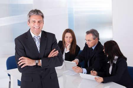 Foto de Happy Mature Businessman Standing In Front Of Colleagues In Office - Imagen libre de derechos