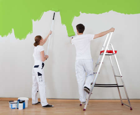 Photo pour Portrait Of Young Couple Painting Wall Together - image libre de droit
