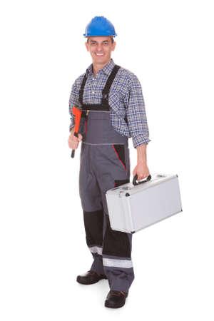 Foto de Happy Male Worker Holding Worktool Over White Background - Imagen libre de derechos
