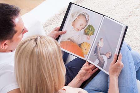 Foto de Portrait Of Couple Looking At Photo Album - Imagen libre de derechos