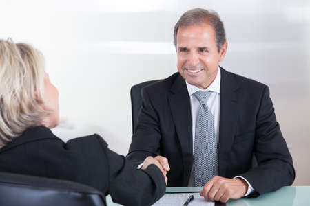 Photo for Handshake Of Mature Businesswoman And Businessman In Office - Royalty Free Image