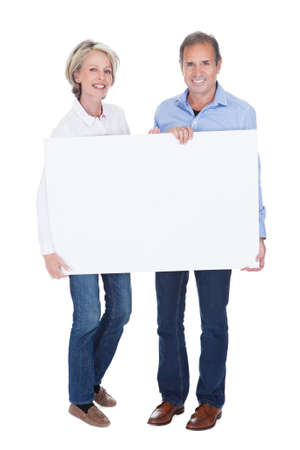 Photo for Happy Mature Couple Holding Blank Placard Isolated Over White Background - Royalty Free Image