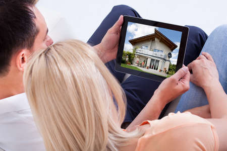 Couple Looking At House On Digital Tablet's Screen