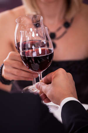 Photo pour Close-up Of Couple's Hand Holding Red Wine And Toasting Glass - image libre de droit